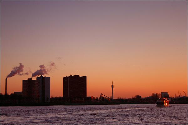 Stroomafwaarts - Boot op de Maas tegen een ondergaande zon